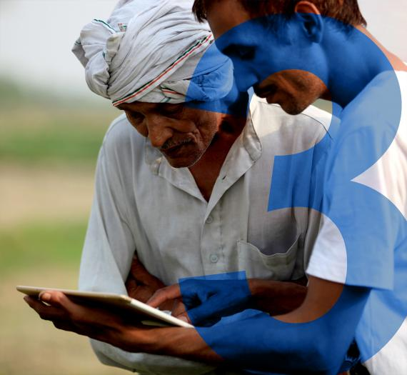 3. two men in a field checking information on a tablet